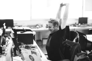 Man happily stretching at work