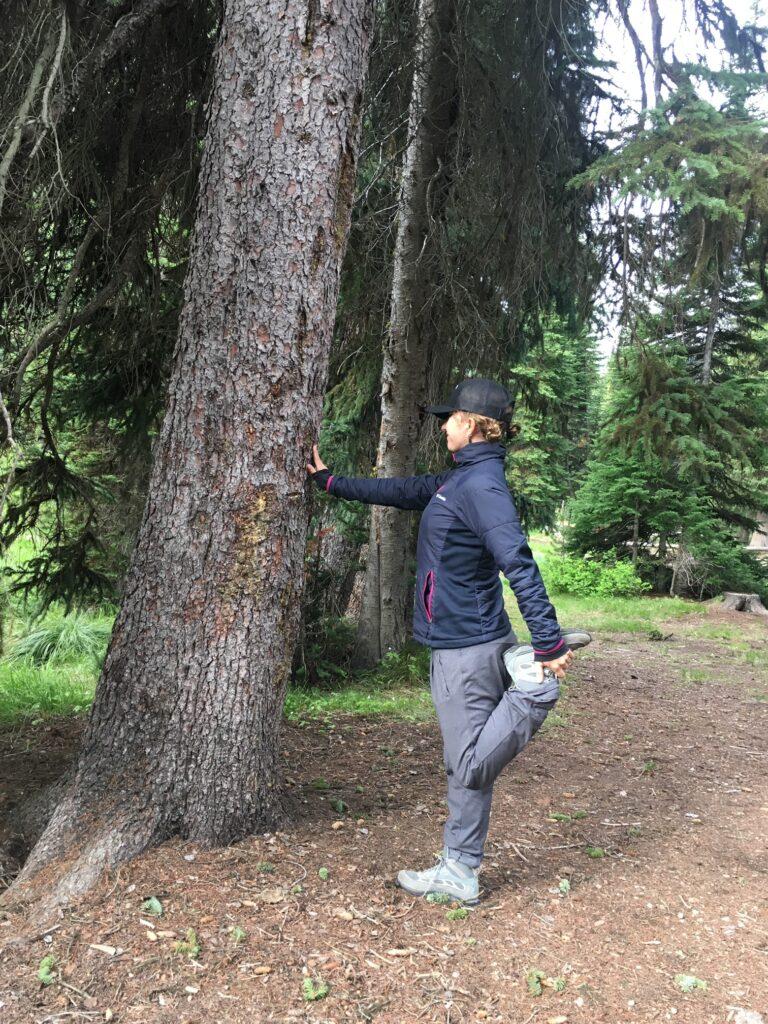 Quad stretch using tree for balance